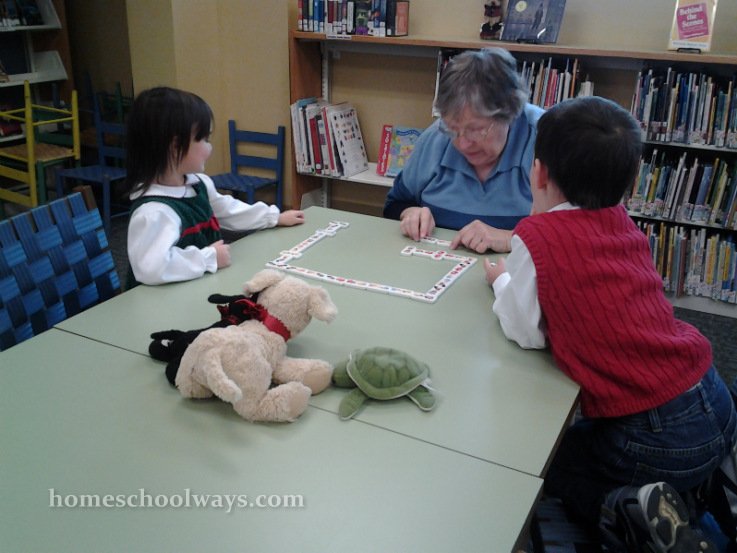 Children's librarian plays dominoes with boy and girl