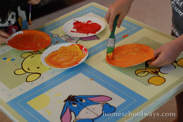 Children mix red and yellow paint to obtain orange.