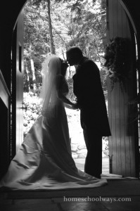 Bride and groom kissing in the church doorway