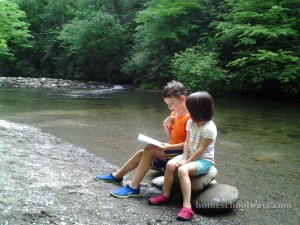 Boy and girl sitting on rocks and reading by the river