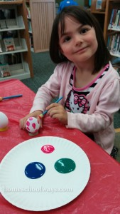 Little girl painting an Easter Egg at the Library