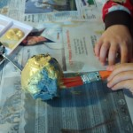 Child painting a golden apple craft