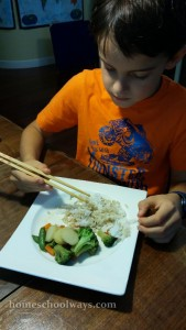 Boy eating with chopsticks