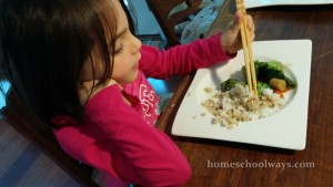 Girl eating with chopsticks