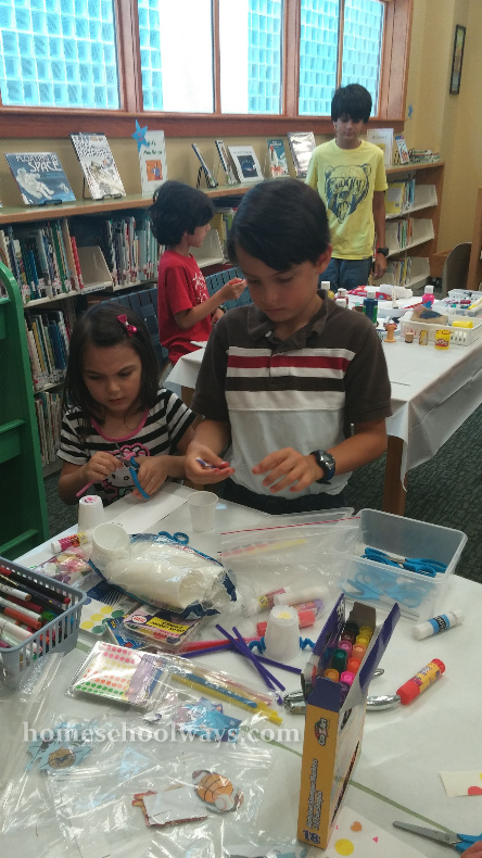 Boy and girl working on a craft at the library