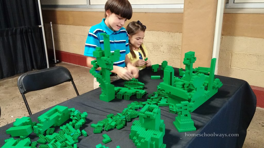 Boy and girl building with green LEGO bricks