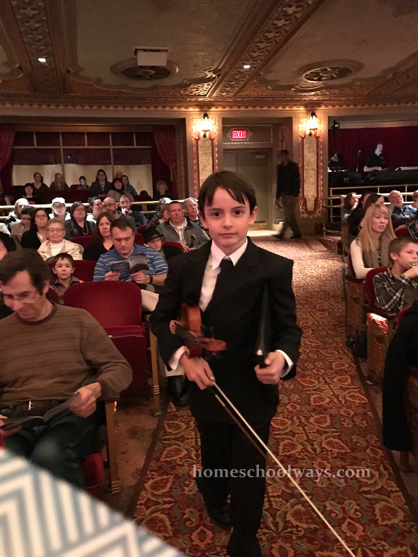 Boy walks with his violin at Tennessee Theater
