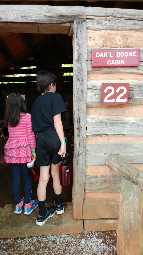 Boy and girl enter the Dan'l Boone cabin