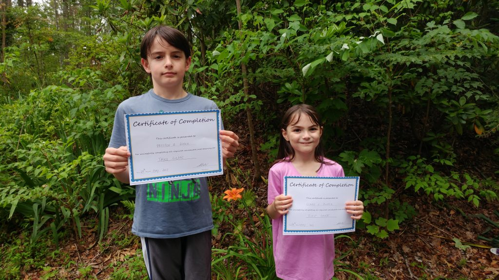 Boy and girl holding homeschool certificates of completion