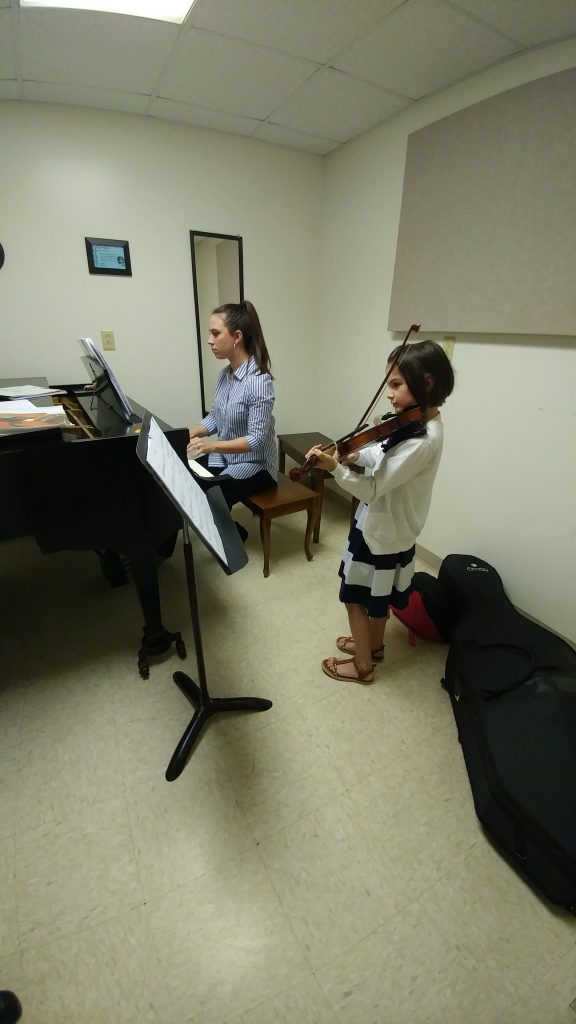 Girl violinist practices with pianist