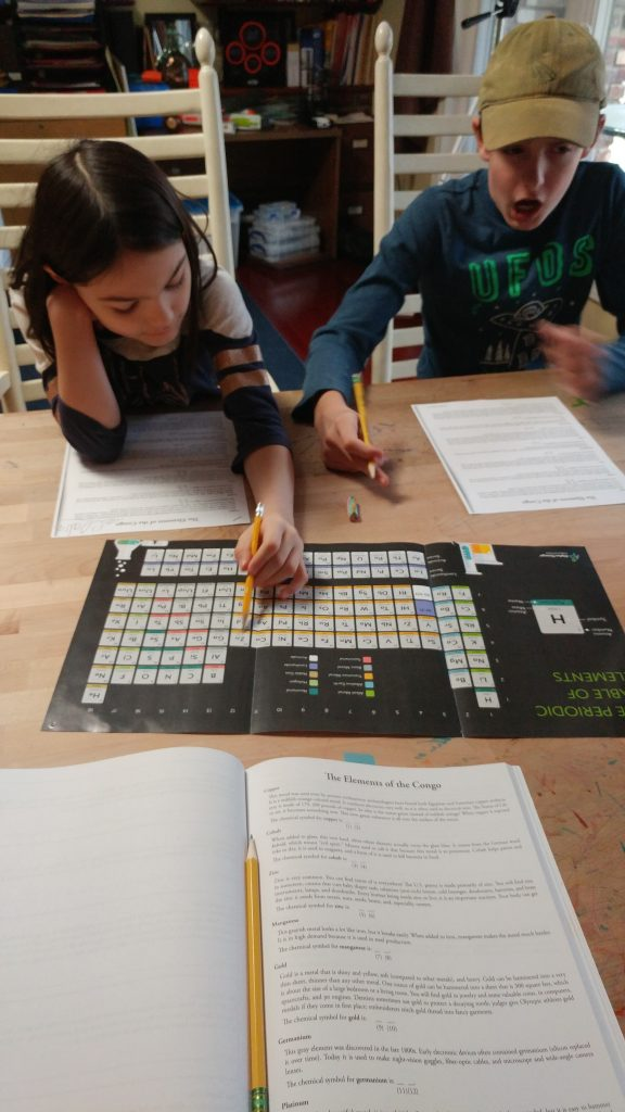 Boy and girl looking up chemical elements