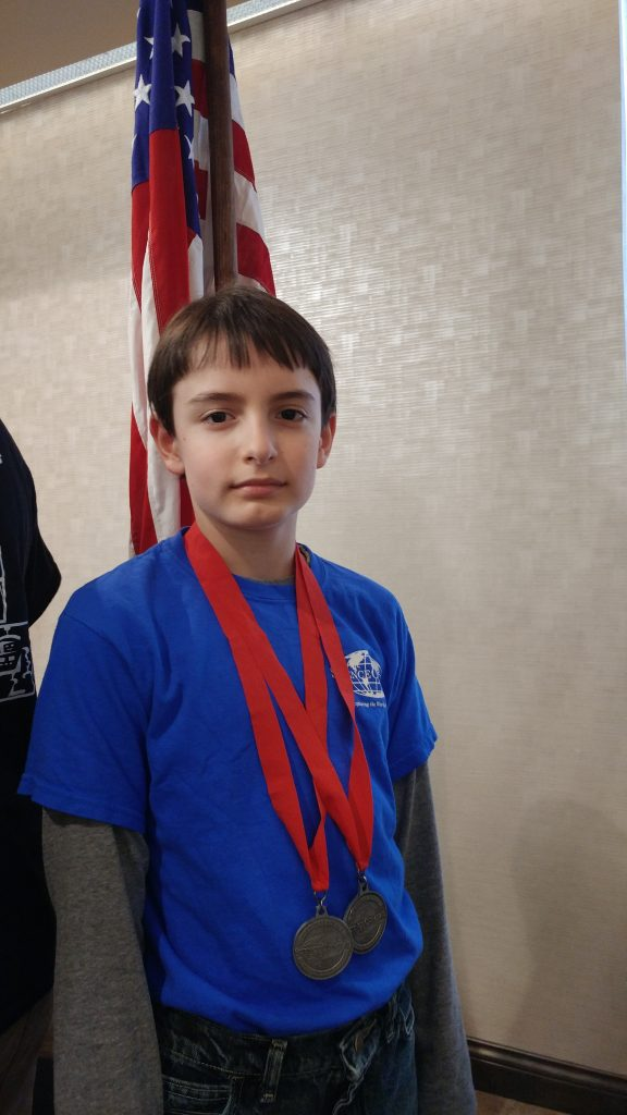 Boy with Science Olympiad medals