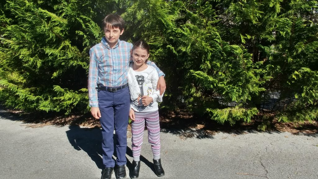 Boy and girl in front of evergreens