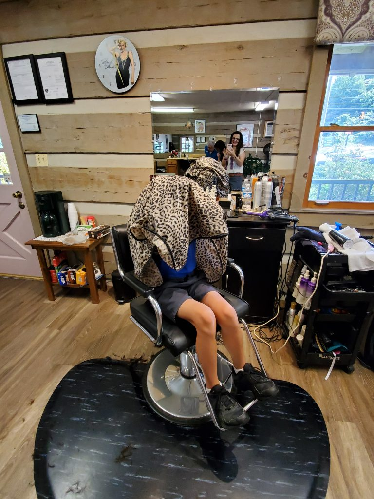 Boy hides behind cape at hairdresser's.
